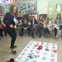 Teachers practice teaching the alphabet and vocabulary to children using the mat game on a Smart Teachers Play More Course