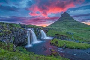 Waterfalls and a mountain in the evening sky.