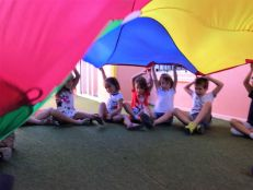 Happy children learning vocabulary and honing fine motor skills with the parachute game.