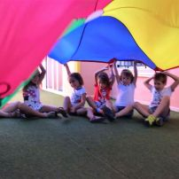 happy children sitting in a circle on the floor playing the parachute game