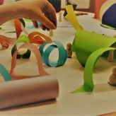 Kids playing with scraps of paper to make a mini world