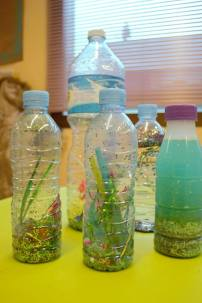 plastic bottle filled with colourful objects made by children to use as shakers