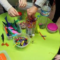 Children making colourful shakers with natural resources
